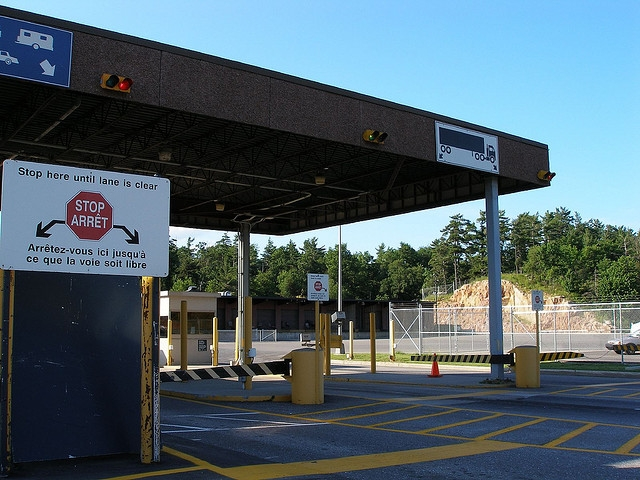 highway border crossing, with stop here sign