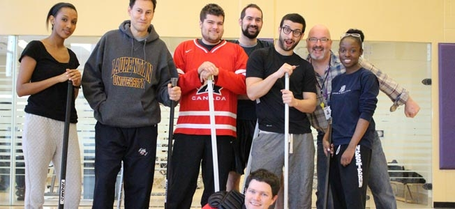 TVO and CAMH staff with their floor hockey sticks - goalie lies down in front of the group
