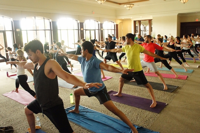 Room full of people doing yoga, warrior pose