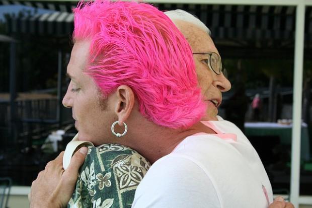 Pink haired man hugging an senior woman
